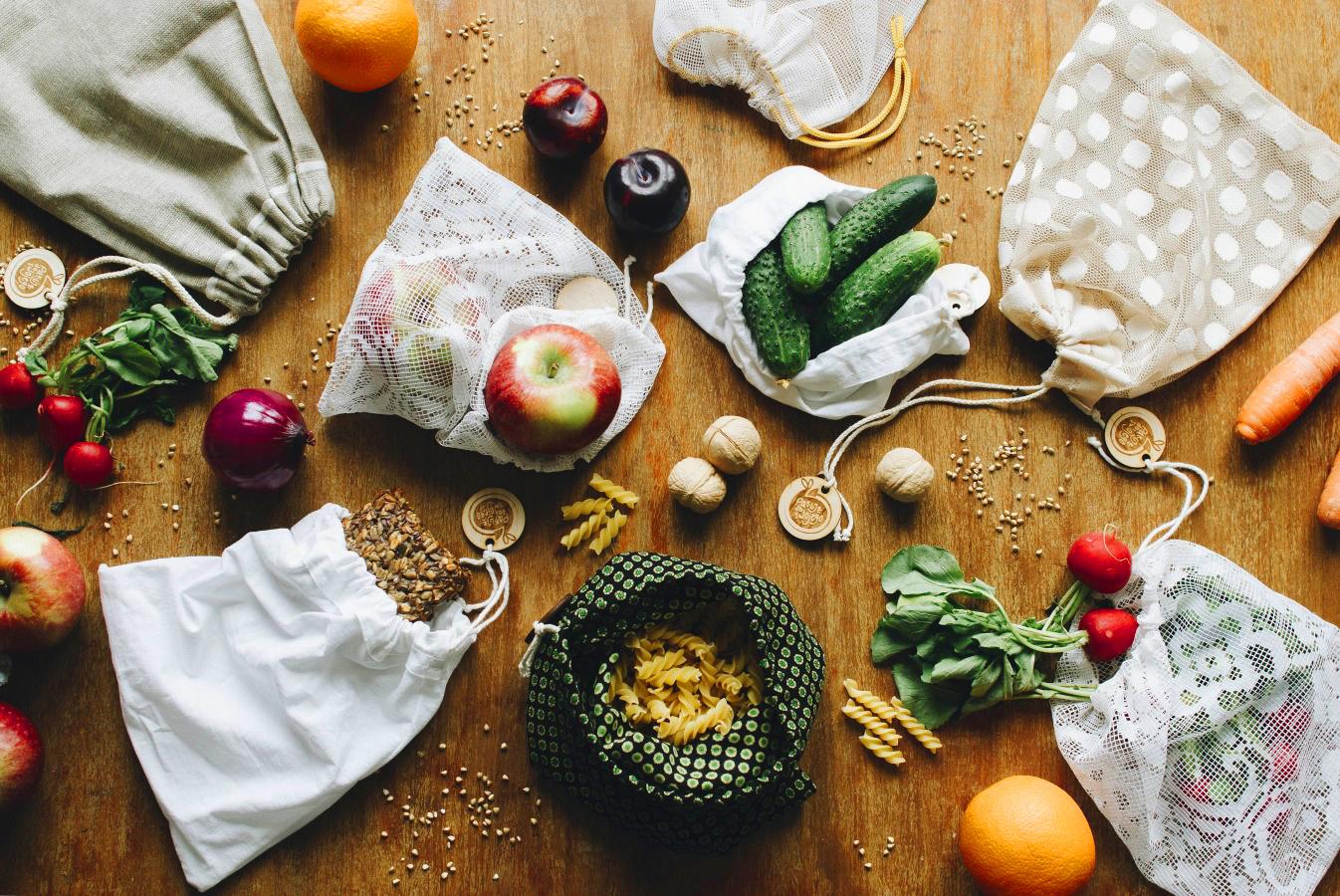 Zakupy w woreczkach wielorazowych, jabłka, ogórki, makaron, pieczywo.